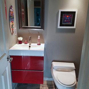 Idee per un piccolo bagno di servizio contemporaneo con ante lisce, ante rosse, WC monopezzo, piastrelle marroni, piastrelle in gres porcellanato, pareti grigie, pavimento in gres porcellanato, lavabo integrato e top in superficie solida
