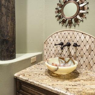 Aménagement d'un petit WC et toilettes sud-ouest américain avec un placard avec porte à panneau surélevé, un WC à poser, un carrelage beige, un mur vert, un sol en carrelage de céramique, une vasque, un plan de toilette en granite, du carrelage en travertin et des portes de placard en bois sombre.