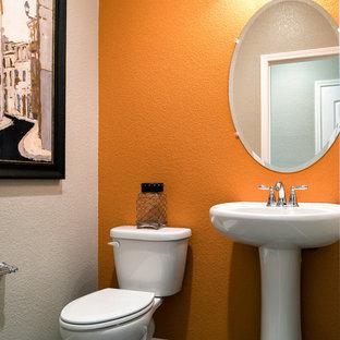 Modelo de aseo minimalista, de tamaño medio, con sanitario de una pieza, baldosas y/o azulejos grises, baldosas y/o azulejos de cerámica, parades naranjas y lavabo con pedestal