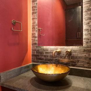 Foto di un piccolo bagno di servizio minimal con ante con riquadro incassato, ante in legno bruno, piastrelle marroni, piastrelle di vetro, pareti rosse, pavimento in legno massello medio, lavabo a bacinella, top in saponaria, pavimento marrone e top nero