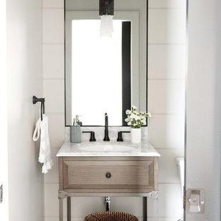 Пример оригинального дизайна: туалет среднего размера в стиле кантри с фасадами в стиле шейкер, коричневыми фасадами, унитазом-моноблоком, белыми стенами, врезной раковиной, серым полом и бежевой столешницей