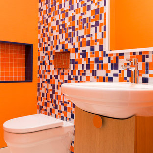 Inspiration for a small midcentury cloakroom in Houston with flat-panel cabinets, light wood cabinets, a wall mounted toilet, multi-coloured tiles, ceramic tiles, orange walls, an integrated sink and porcelain flooring.