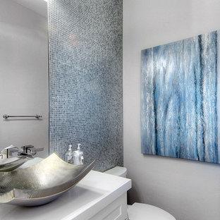 Свежая идея для дизайна: туалет среднего размера в стиле современная классика с белыми фасадами, унитазом-моноблоком, синей плиткой, серыми стенами, настольной раковиной, столешницей из искусственного кварца и стеклянной плиткой - отличное фото интерьера