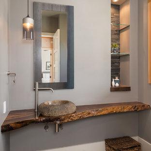 Immagine di un bagno di servizio stile rurale di medie dimensioni con lavabo a bacinella, top in legno, pareti grigie, pavimento in cemento e top marrone
