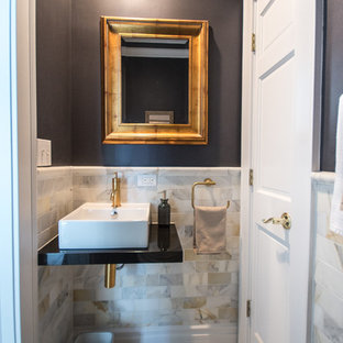 Photo of a medium sized traditional cloakroom in Chicago with multi-coloured tiles, marble tiles, grey walls, ceramic flooring, a vessel sink, solid surface worktops, brown floors and a two-piece toilet.