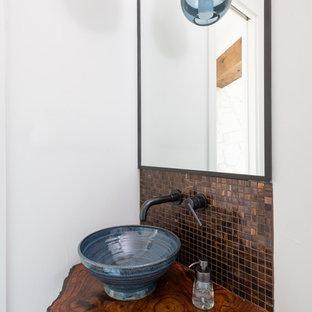 Cette photo montre un WC et toilettes sud-ouest américain de taille moyenne avec un carrelage marron, carrelage en mosaïque, un mur blanc, une vasque, un plan de toilette en bois et un plan de toilette marron.