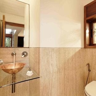 Idée de décoration pour un WC et toilettes design avec du carrelage en travertin.