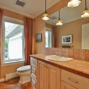 Свежая идея для дизайна: туалет среднего размера в современном стиле с фасадами с выступающей филенкой, желтыми фасадами, раздельным унитазом, бежевой плиткой, керамической плиткой, бежевыми стенами, полом из керамической плитки, накладной раковиной, столешницей из плитки и бежевым полом - отличное фото интерьера