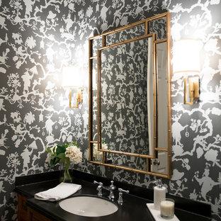 Aménagement d'un petit WC et toilettes classique avec un placard avec porte à panneau surélevé, des portes de placard en bois sombre, un lavabo encastré et un plan de toilette en surface solide.