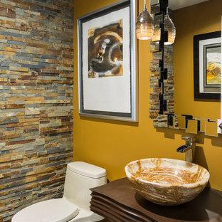 Cette image montre un WC et toilettes design avec un WC à poser, un carrelage multicolore, un carrelage de pierre, un mur jaune, un sol en bois foncé, une vasque, un plan de toilette en bois et un plan de toilette marron.