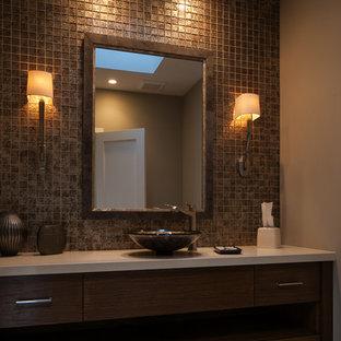 Diseño de aseo contemporáneo, grande, con armarios con paneles lisos, puertas de armario de madera en tonos medios, baldosas y/o azulejos marrones, baldosas y/o azulejos de vidrio, paredes beige, suelo de travertino, lavabo sobreencimera y encimera de acrílico