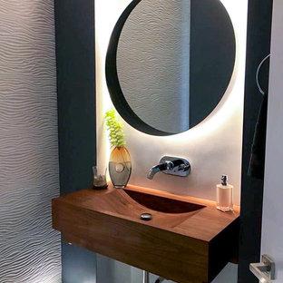 Свежая идея для дизайна: туалет в стиле модернизм с коричневыми фасадами, серыми стенами, полом из керамической плитки, столешницей из дерева и серым полом - отличное фото интерьера