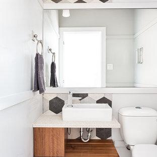 Источник вдохновения для домашнего уюта: маленький туалет в современном стиле с плоскими фасадами, темными деревянными фасадами, раздельным унитазом, белыми стенами, настольной раковиной, разноцветным полом, белой столешницей, черной плиткой, керамогранитной плиткой, полом из керамогранита и столешницей из искусственного кварца