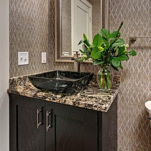 Cette photo montre un petit WC et toilettes tendance avec un placard en trompe-l'oeil, des portes de placard noires, un mur multicolore, un sol en bois brun, une vasque, un plan de toilette en granite, un sol marron et un plan de toilette multicolore.