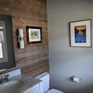 Immagine di un bagno di servizio tradizionale con ante con riquadro incassato, ante gialle, WC a due pezzi, piastrelle marroni, pareti grigie, lavabo sottopiano, top in marmo e top bianco