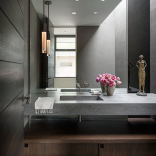 Midcentury powder room in Orange County with flat-panel cabinets, dark wood cabinets, grey walls, dark hardwood floors, an integrated sink, brown floor and grey benchtops.