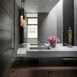 Modelo de aseo vintage con armarios con paneles lisos, puertas de armario de madera en tonos medios, paredes grises, suelo de madera oscura, lavabo integrado, suelo marrón y encimeras grises