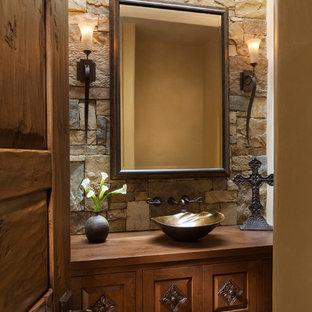 Diseño de aseo de estilo americano con armarios tipo mueble, puertas de armario de madera oscura, lavabo sobreencimera y suelo marrón