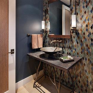 На фото: туалет среднего размера в стиле рустика с бежевой плиткой, синей плиткой, коричневой плиткой, серой плиткой, оранжевой плиткой, разноцветной плиткой, синими стенами, полом из известняка, настольной раковиной, столешницей из дерева и коричневой столешницей