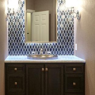 Bild på ett mellanstort vintage toalett, med ett nedsänkt handfat, skåp i mörkt trä, bänkskiva i kvartsit, en toalettstol med separat cisternkåpa, blå kakel, keramikplattor, grå väggar och luckor med infälld panel