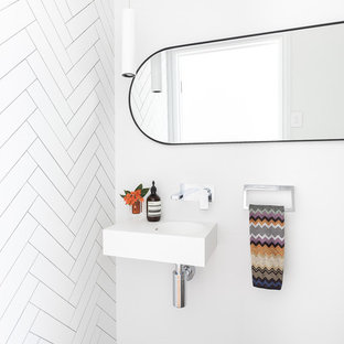 Design ideas for a mid-sized contemporary powder room in Brisbane with a one-piece toilet, white tile, ceramic tile, white walls, cement tiles, a wall-mount sink, engineered quartz benchtops, grey floor and white benchtops.