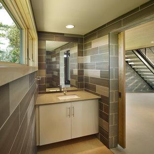 Exemple d'un petit WC et toilettes tendance avec un lavabo encastré, un placard à porte plane, des portes de placard beiges, un plan de toilette en surface solide, un carrelage gris, des carreaux de porcelaine, un mur gris, un sol en contreplaqué et un plan de toilette beige.