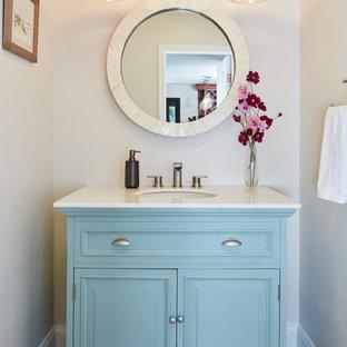 Foto de aseo actual, pequeño, con armarios tipo mueble, puertas de armario azules, encimera de mármol, paredes beige, lavabo bajoencimera, suelo beige, suelo de travertino y encimeras blancas