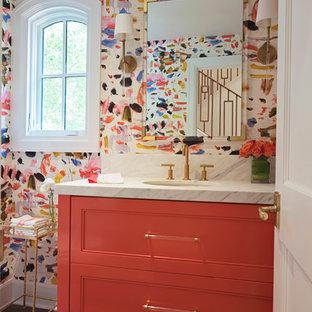 Réalisation d'un WC et toilettes tradition de taille moyenne avec un placard à porte affleurante, des portes de placard oranges, un mur multicolore, un sol en bois brun, un lavabo encastré, un plan de toilette en marbre et un sol marron.