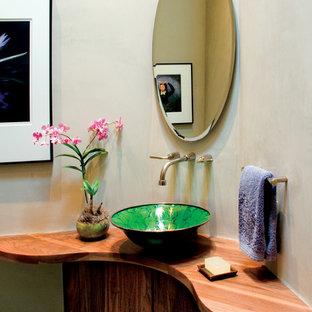 Mediterrane Gästetoilette mit flächenbündigen Schrankfronten, dunklen Holzschränken, beiger Wandfarbe, Aufsatzwaschbecken und Waschtisch aus Holz in Albuquerque