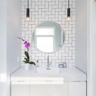 Kleine Moderne Gästetoilette mit flächenbündigen Schrankfronten, weißen Schränken, weißen Fliesen, Metrofliesen, weißer Wandfarbe, integriertem Waschbecken und weißer Waschtischplatte in Toronto