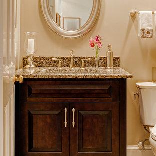 Réalisation d'un petit WC et toilettes tradition avec un lavabo encastré, un placard avec porte à panneau surélevé, des portes de placard en bois sombre, un plan de toilette en granite, un WC séparé, un carrelage multicolore, un sol en carrelage de porcelaine et un mur beige.