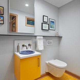 Foto de aseo actual con armarios con paneles lisos, puertas de armario amarillas, sanitario de pared, paredes grises, lavabo encastrado, suelo amarillo y encimeras blancas