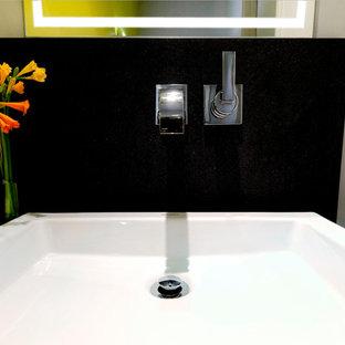 Cette photo montre un petit WC et toilettes tendance avec un placard à porte plane, des portes de placard en bois clair, un WC à poser, un carrelage jaune, un mur jaune, un sol en carrelage de céramique, une vasque, un plan de toilette en granite, un sol noir et un plan de toilette noir.