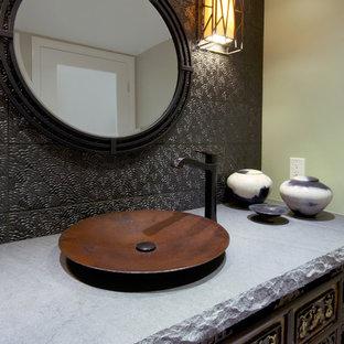 На фото: с высоким бюджетом маленькие туалеты в восточном стиле с фасадами островного типа, темными деревянными фасадами, коричневой плиткой, полом из керамогранита, настольной раковиной, металлической плиткой, бежевыми стенами и серой столешницей
