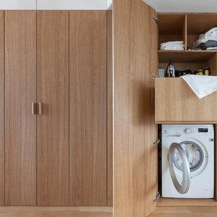 Modern inredning av en liten liten tvättstuga med garderob, med mellanmörkt trägolv, släta luckor, skåp i mellenmörkt trä och brunt golv