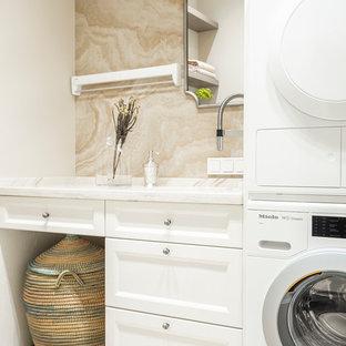 На фото: прачечная в стиле неоклассика (современная классика) с фасадами с утопленной филенкой, белыми фасадами, белыми стенами и с сушильной машиной на стиральной машине