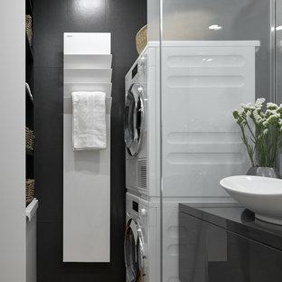 На фото: прачечная в современном стиле с черными стенами и вертикальным расположением стиральной и сушильной машин с