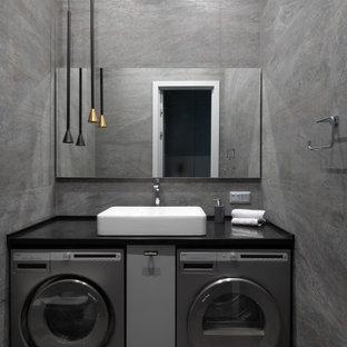 Стильный дизайн: большая прачечная в современном стиле с серыми стенами, полом из ламината и серым полом - последний тренд