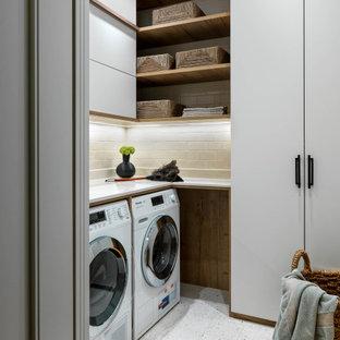 Idee per una piccola sala lavanderia minimal con ante lisce, ante bianche, top in marmo, lavatrice e asciugatrice affiancate, pavimento bianco e top bianco