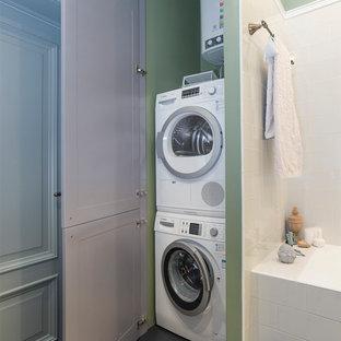 На фото: прачечная в стиле современная классика с зелеными стенами и с сушильной машиной на стиральной машине с