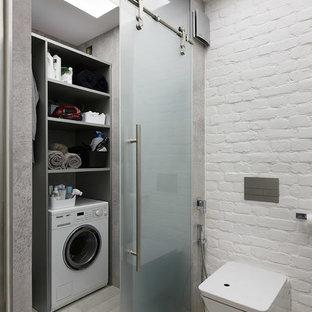 Aménagement d'une buanderie industrielle avec un placard et un mur gris.