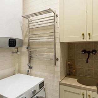 Foto på en liten eklektisk beige l-formad tvättstuga enbart för tvätt, med en allbänk, luckor med infälld panel, beige skåp, bänkskiva i koppar, brunt stänkskydd, stänkskydd i keramik, beige väggar, klinkergolv i porslin, en tvättmaskin och torktumlare bredvid varandra och beiget golv
