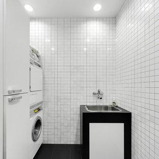 На фото: отдельная, прямая прачечная в современном стиле с накладной раковиной, плоскими фасадами, с сушильной машиной на стиральной машине, черным полом, черной столешницей, белыми фасадами и белыми стенами с