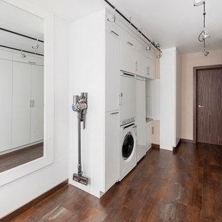На фото: параллельная универсальная комната в современном стиле с плоскими фасадами, белыми фасадами, с сушильной машиной на стиральной машине, коричневым полом и белыми стенами с