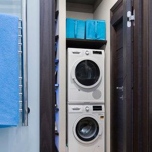 Exemple d'une petite buanderie tendance multi-usage avec un mur gris, un sol en bois brun, des machines superposées et un sol beige.