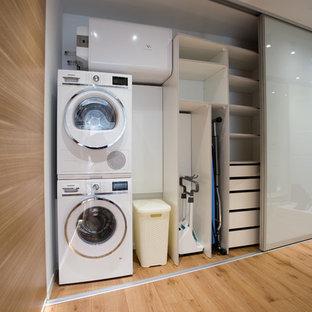 На фото: кладовки в современном стиле с белыми стенами, с сушильной машиной на стиральной машине и коричневым полом