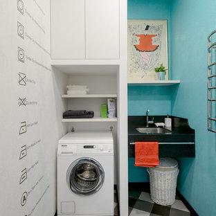 Ispirazione per una piccola sala lavanderia minimal con lavello sottopiano, nessun'anta, ante bianche e pareti blu