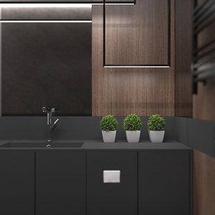 Exempel på en mellanstor modern svarta linjär svart tvättstuga enbart för tvätt och med garderob, med en integrerad diskho, släta luckor, svarta skåp, bänkskiva i koppar, svarta väggar, klinkergolv i keramik och grått golv