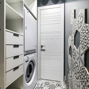 На фото: отдельная прачечная в современном стиле с черными стенами и вертикальным расположением стиральной и сушильной машин с