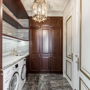 Idéer för en mellanstor klassisk grå l-formad tvättstuga enbart för tvätt, med en undermonterad diskho, luckor med infälld panel, skåp i mörkt trä, bänkskiva i onyx, grått stänkskydd, stänkskydd i marmor, grå väggar, klinkergolv i porslin, en tvättmaskin och torktumlare bredvid varandra och grått golv